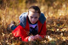 Angry sight of the girl in autumn park. - stock photo
