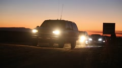 Vehicles Silhouette Drive in Remote Desert with Sunset Stock Footage