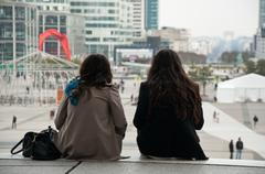 women sitting on stairs in La defense arch - stock photo