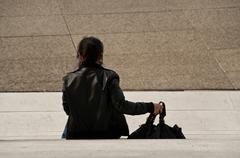 woman sitting on stairs in La defense arch - stock photo