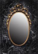 Antique golden frame enchanted mirror on black marble background - stock photo