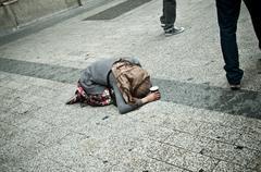 Stock Photo of poor woman kneeling in the street