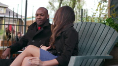 A couple getting comfortable on a park bench, slow motion - stock footage
