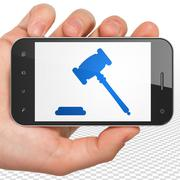 Stock Illustration of Law concept: Hand Holding Smartphone with Gavel on display