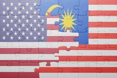 puzzle with the national flag of united states of america and malaysia - stock photo