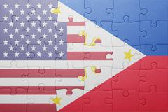 puzzle with the national flag of united states of america and philippines - stock photo