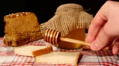 Honey spoon dripper, jar with stick pouring over toast bread, honeycomb on black Stock Footage