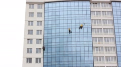 Window washers working on a tall building Stock Footage