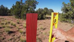 Checking Angle Of Fence Post With Carpenters Level Stock Footage