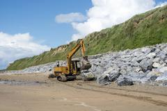 mechanical excavator working on coastal protection - stock photo
