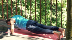 Young man doing push-ups on mat on terrace  Stock Footage