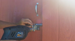 Drilling Hole For Locking Mechanism On Shed Door Stock Footage