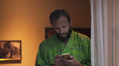 Young man in bathrobe using smartphone by window at home Stock Footage