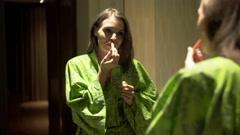 Pretty woman in bathrobe applying lipstick in bathroom - stock footage