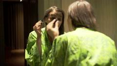 Pretty woman in bathrobe applying mascara in bathroom Stock Footage