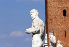 ancient marble white statue and big tower in background - stock photo