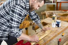 Craftsman sanding a guitar neck in wood at workshop Stock Photos