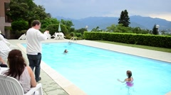 Children swimming in the pool against the backdrop of the Alps - Italy Stock Footage