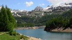 Alpine Lake Reservoir on a background of snow-capped peaks of Alps Stock Footage