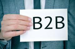 man in suit shows a signboard with the word B2B - stock photo
