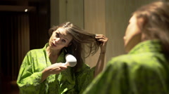 Young, pretty woman in bathrobe drying her hair in bathroom - stock footage