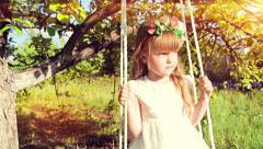 Young girl with wreath of flower sits on a swing under tree Stock Footage