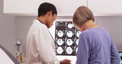 African female doctor reviewing x-ray scans with a senior patient - stock footage
