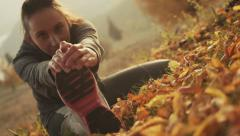 Sportswoman sport stretching in autumn leaves - stock footage