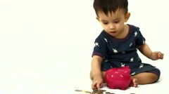 11 months old baby boy putting money in piggy bank Stock Footage