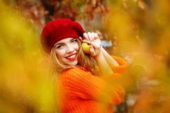 Lovely girl in beret and sweater, holding ripe apple and smiling. Stock Photos