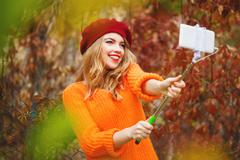 Lovely girl in beret and sweater is doing self-portrait on phone. Stock Photos