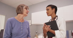Female black doctor discussing health with female white patient Stock Footage