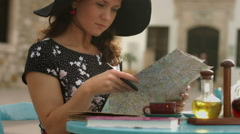 Elegant young female in cafe planning tour abroad, studying map, checking routes Stock Footage