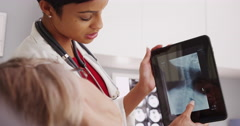 Stock Video Footage of Female African American doctor reviewing x-ray with mature patient