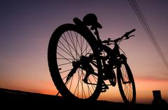 Stock Photo of Silhouette of mountain bike parking on jetty beside sea with sunset sky backg