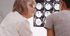 Stock Video Footage of Experienced radiologist and patient looking at x rays