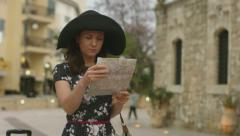 Young woman with luggage and map in hands got lost, finds the right direction - stock footage