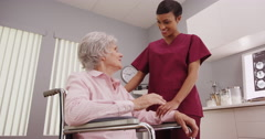 Young attractive nurse showing tablet to elderly patient in a wheelchair Stock Footage