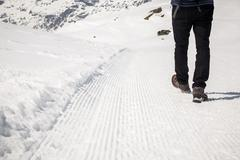 Man in Black walking on the snow footpath. Stock Photos
