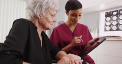 Elderly white woman and young black nurse looking at a tablet Stock Footage