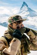 A man in camouflage winter coat standing in front of the background of Matter - stock photo