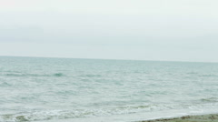 Serious young woman with concentrated face expression running along sea beach - stock footage