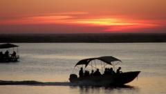 Sunset over lake with boats passing CU Stock Footage