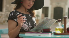 Happy young woman looking for interesting places to see, writing notes on map Stock Footage