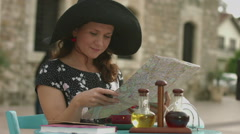 Young woman traveling abroad, planning trip with map in hands, searching sights Stock Footage