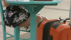 Beautiful female sitting at street cafe table with luggage, examining city map Stock Footage