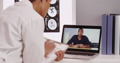 Beautiful female doctor video chatting with patient on laptop Stock Footage
