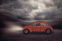 Old little red toy car on a bronze background Stock Photos