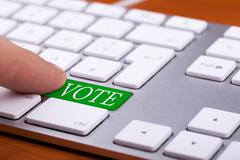 Stock Photo of Finger pressing on vote green button on keyboard