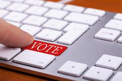 Stock Photo of Finger pressing on vote red button on keyboard